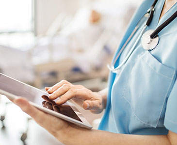 A picture of someone in the medical field using a large tablet