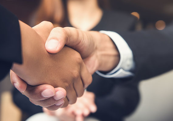 A close up picture of two people shaking hands