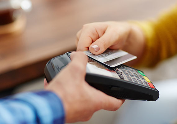 A close up picture of someone making a payment using their card